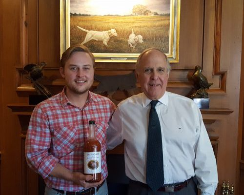 Nat (left) and Pete Hendricks '66, 69L pose with a bottle of Sister's Sauce under a painting depicting the mix's namesake, Sister the bird dog. (Photo: John Ruch)