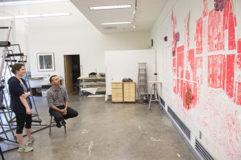 Artist Vincent Valdez critiques Eileen Small's senior art project in Wilson Hall.