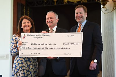 Picture of two class co-chairs presenting a class check to W&L president during reunion weekend in Lee Chapel.
